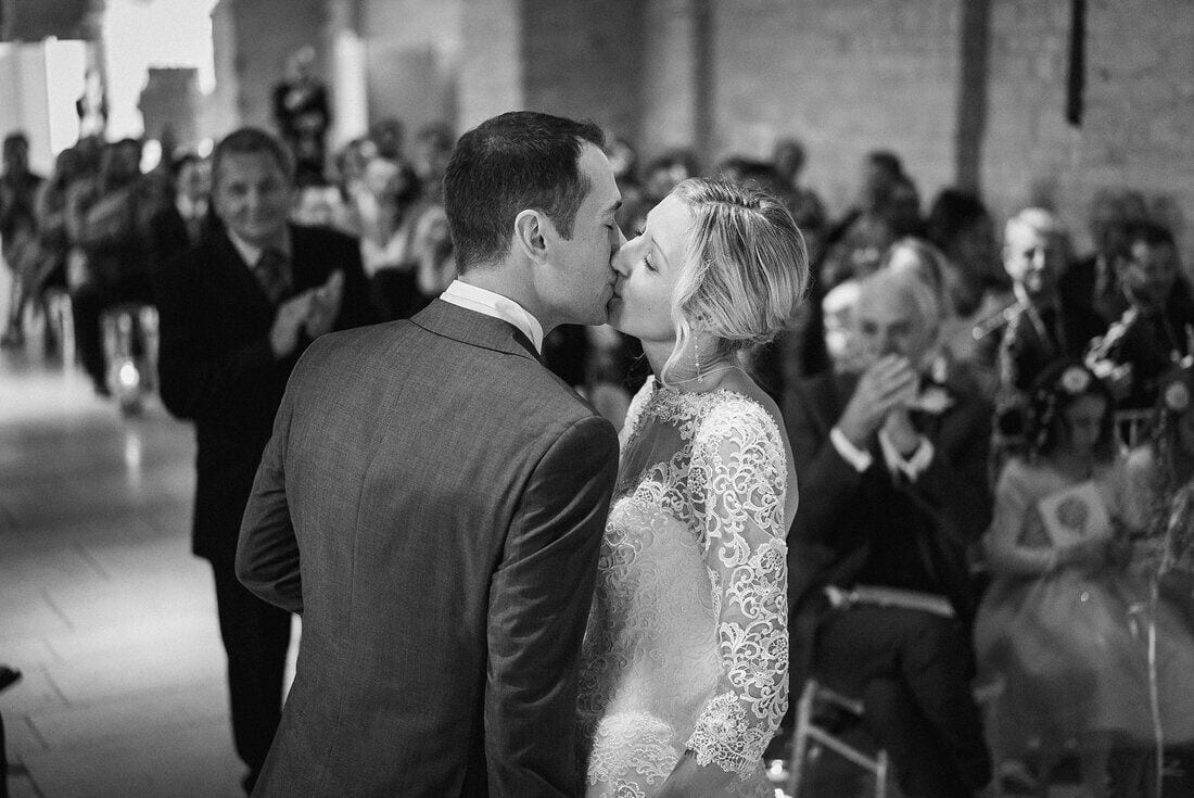The first kiss as husband and wife at the tithe barn hampshire