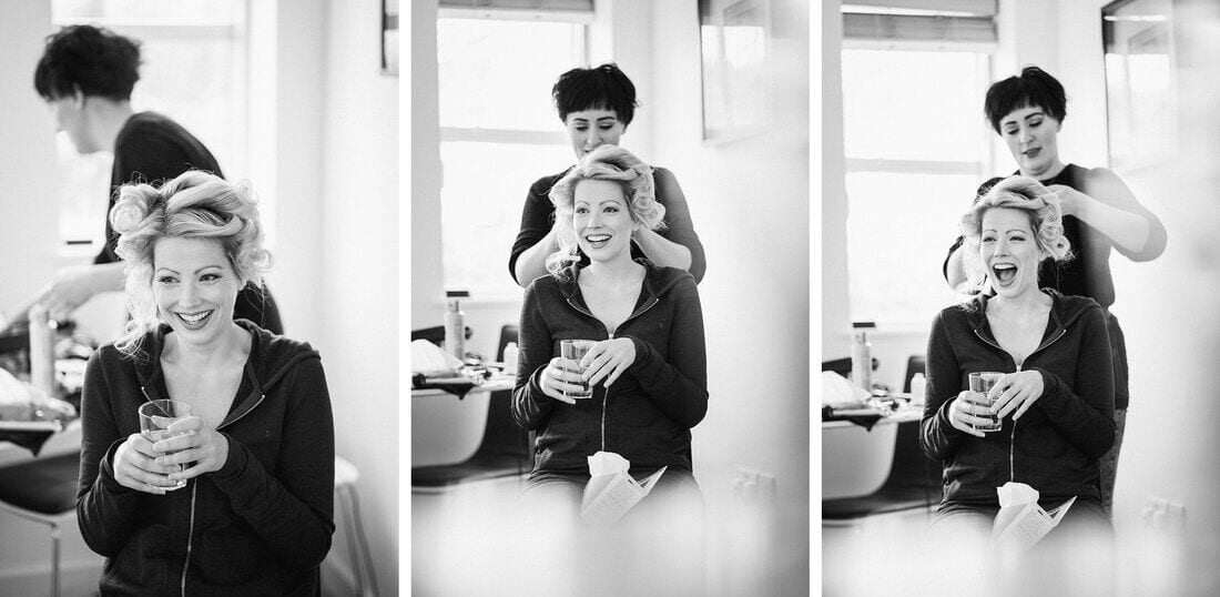 bride laughing while hair and makeup are done