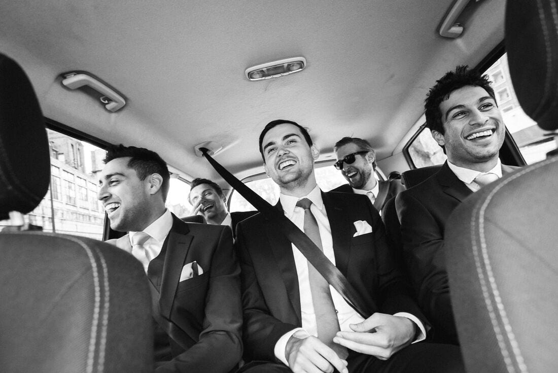 the groomsmen share a joke on the way to the wedding