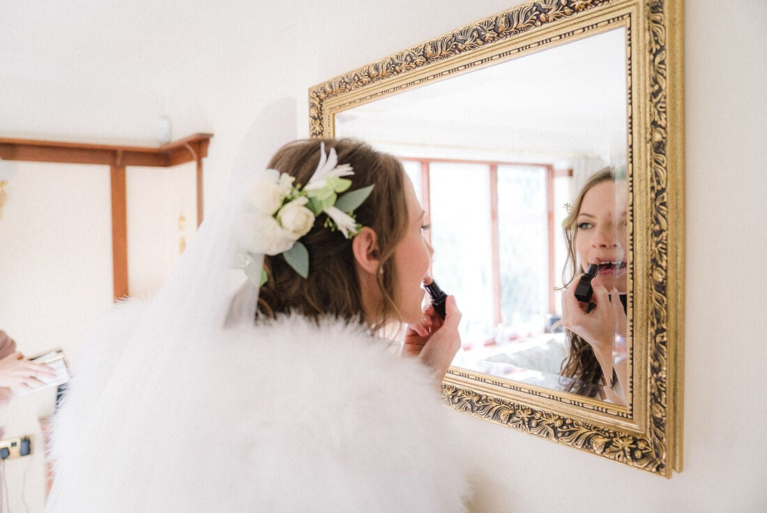 the bride applies her lipstick