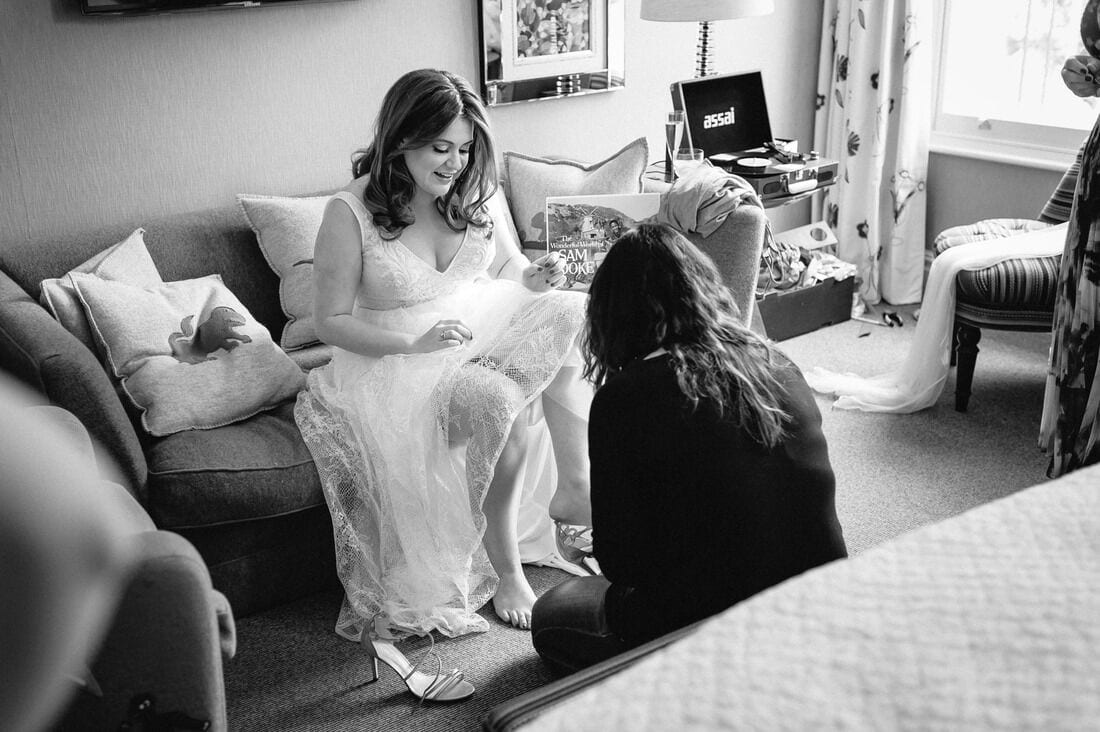 the bride puts on her shoes before her wedding ceremony