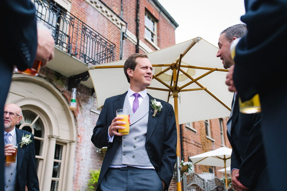 the groom enjoying a drink before his wedding