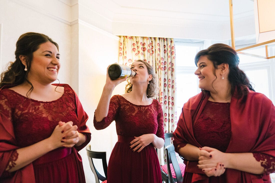 bridesmaids take a swig of champagne