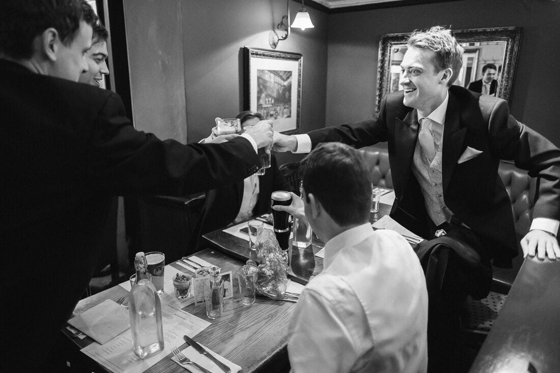 the groomsmen enjoy a pint before the ceremony in wimbledon
