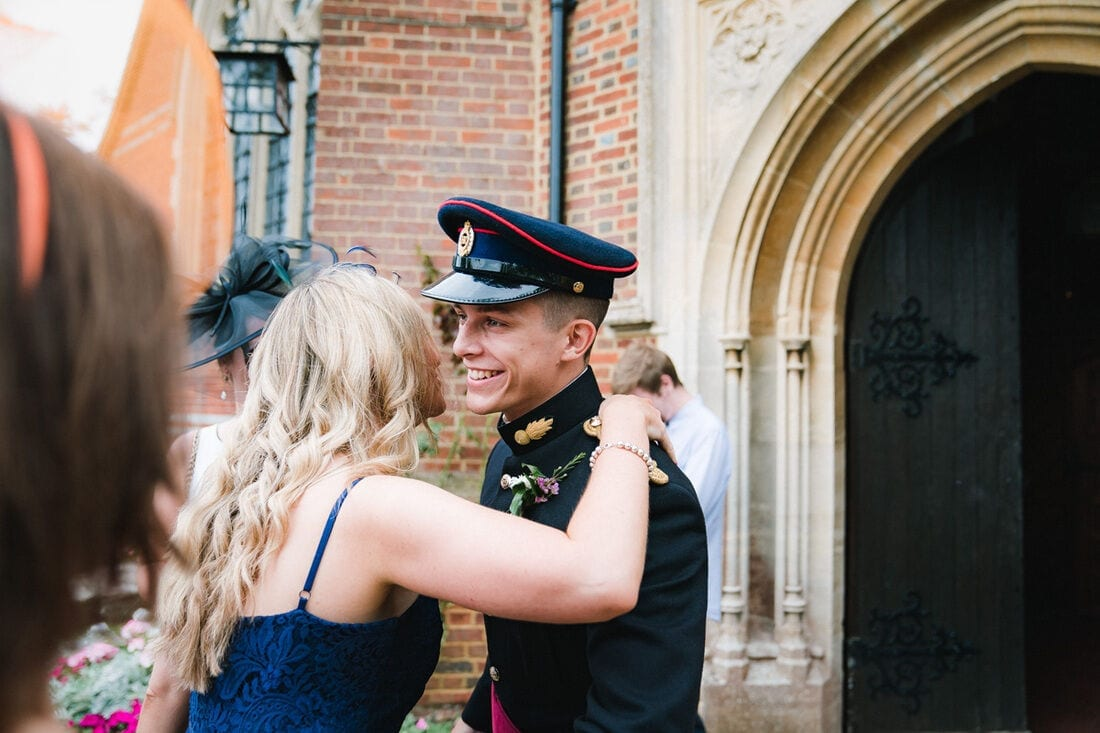 Military groom being greeted by wedding guests