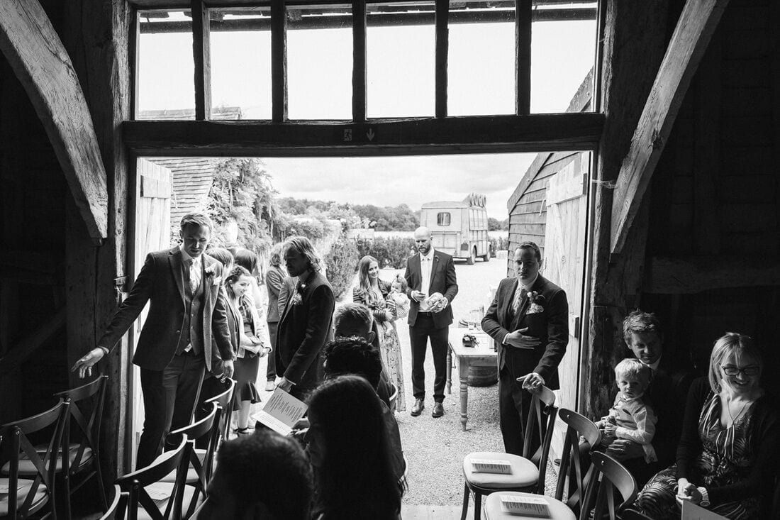wedding guests are seated in the barn at high billinghurst farm