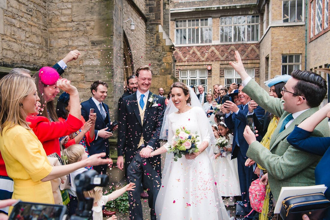 the married couple enjoying confetti outside church