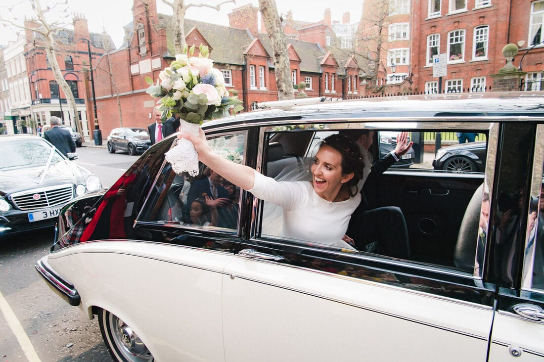 bride waving to the wedding guests