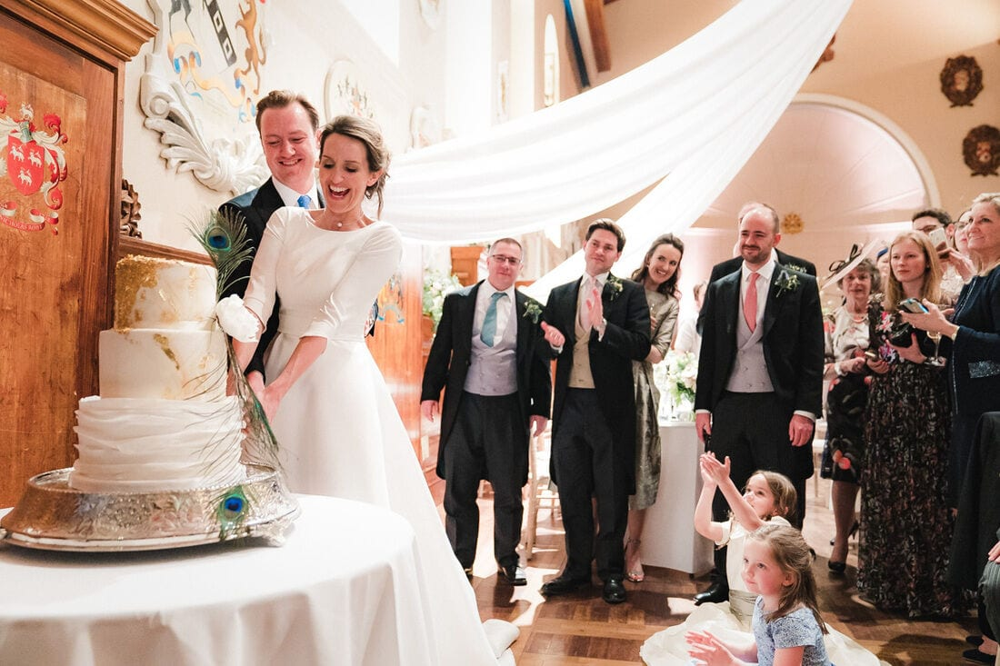 cutting the wedding cake in front of their family and friends