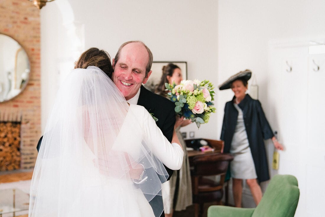 a hug between the bride and her dad before traveling to church