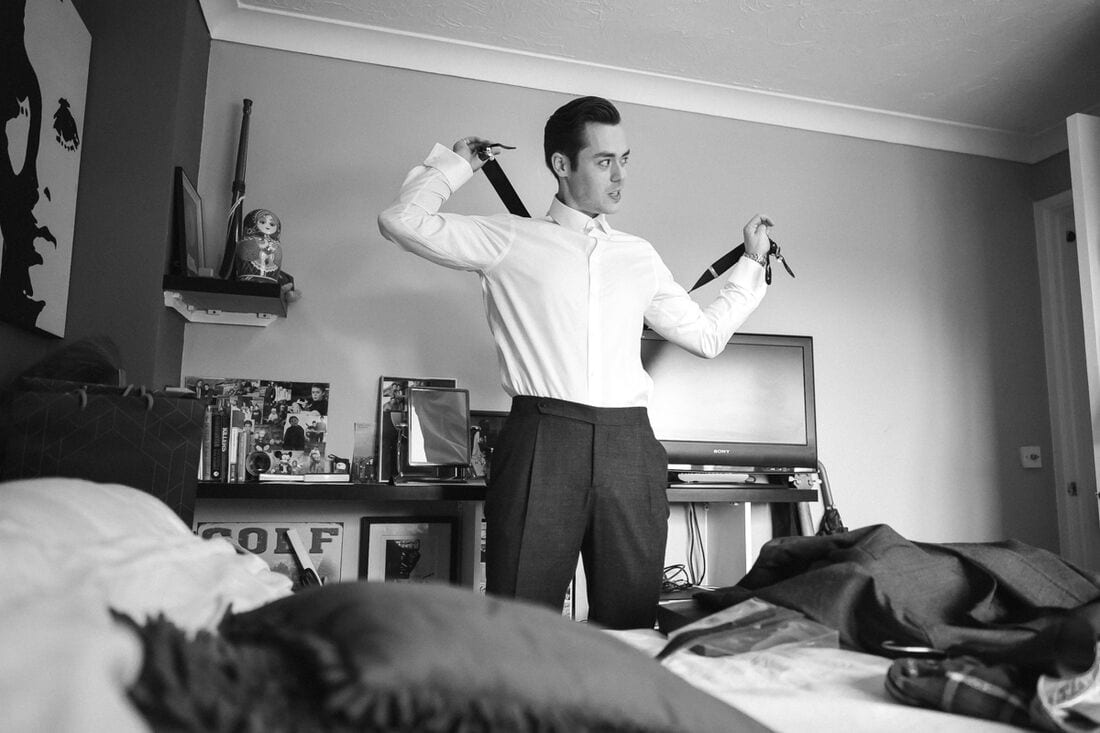 the groom getting dressed for his wedding