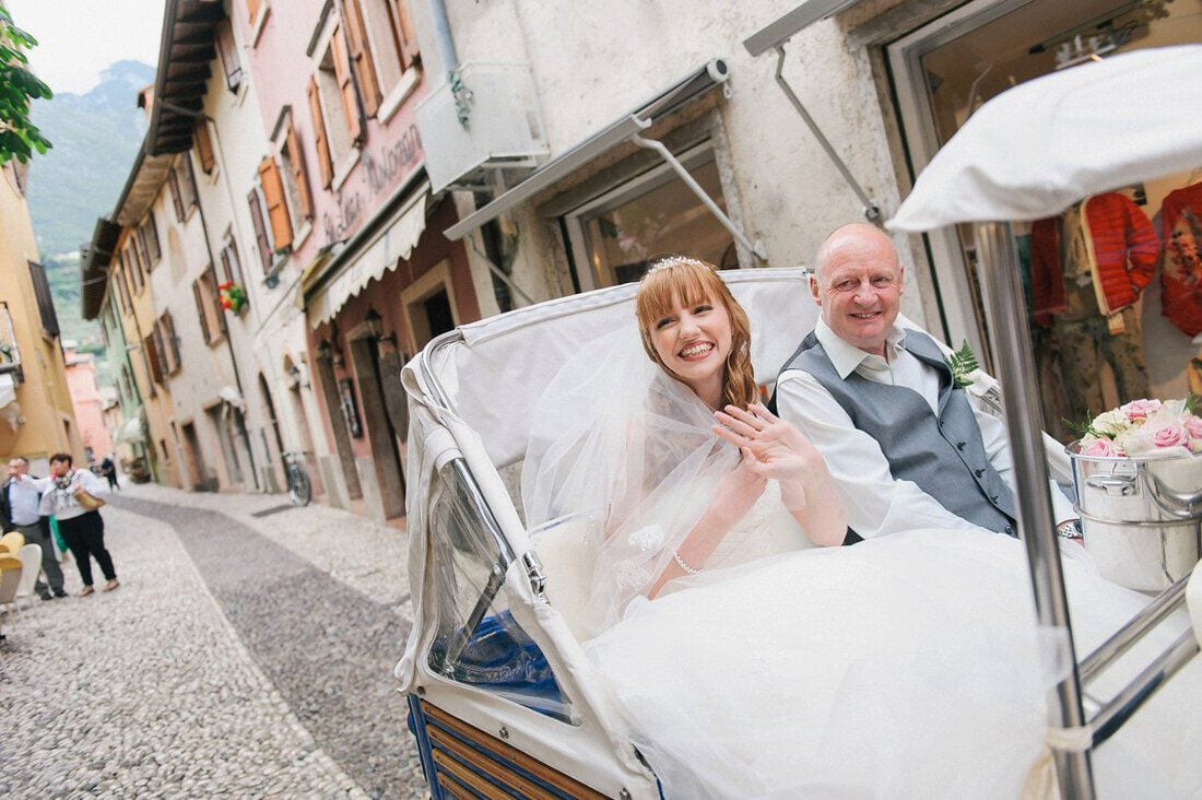 bride and her father ride to wedding through the streets of Malcesine