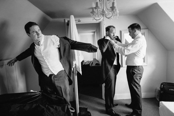 groomsmen getting dressed for the wedding ceremony