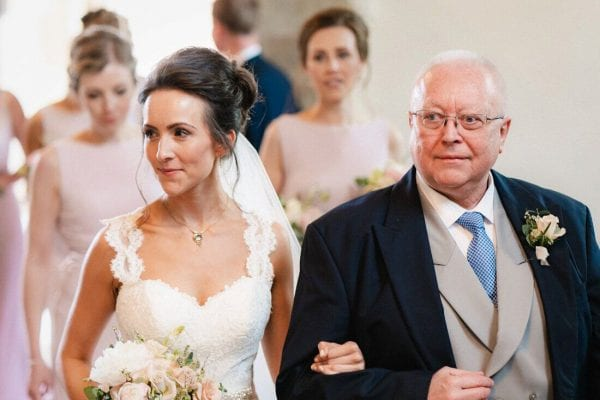 the bride and father walk down the aisle