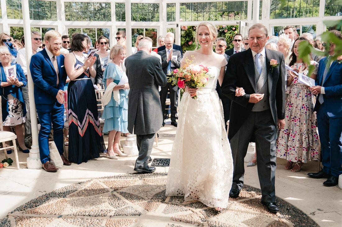all smiles as the bride enters the chiswick house conservatory for her wedding