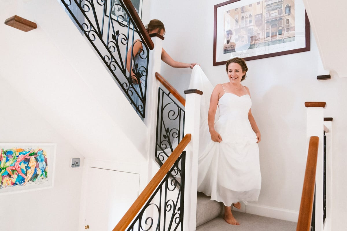 the bride descending the stairs in her dress on the morning of her wedding in Surrey