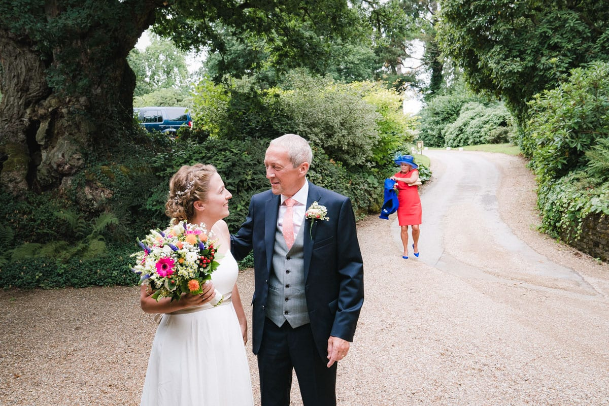 mother and father of the bride arrive at the wedding venue with their daughter on her wedding day