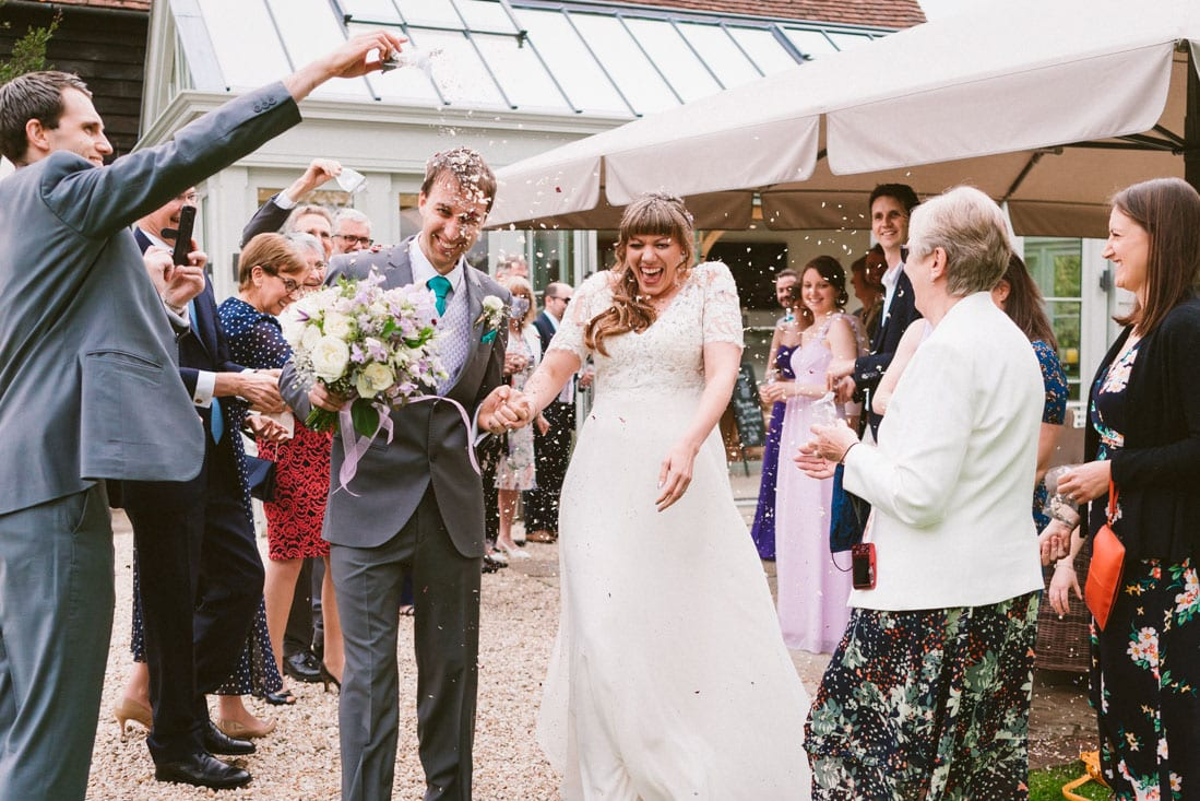 the newleyweds enjoying confetti after getting married at Gate Street Barn