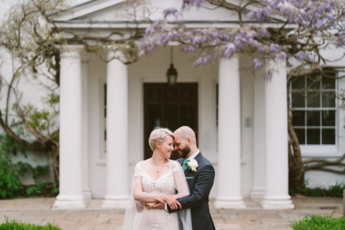 a portrait as husband and wife in front of the Wisteria at Pembroke Lodge